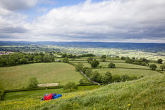 Relaxing in the Countryside. Anonymous person sleeping on the slopes of Glastonbury Tor with beautiful Somerset countryside as a backdrop royalty free stock photo