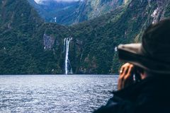 Anonymous person taking pictures of waterfall stock image