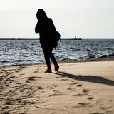 anonymous person walking on a sand at windy beach Royalty Free Stock Photo