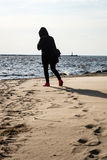 anonymous person walking on a sand at windy beach Stock Images