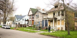 Anonymous Person Walks Sidewalk Derelict Abandoned Houses Detroit. Detroit Michigan boarded up abandoned houses dominate the landscape person walking down the royalty free stock photos