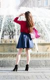 Anonymous pretty girl is standing in front of a fountain. Royalty Free Stock Photo