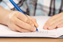 Anonymous pupil hand writing homework Royalty Free Stock Images