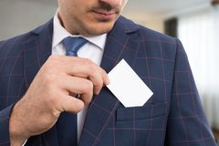 Anonymous salesman placing white card in pocket. Anonymous salesman or businessperson placing white empty card in suit pocket on indoor background royalty free stock images