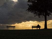Anonymous silhouette of a man on a bench at sunset. A man sits alone on a bench during a cloudy and dark sunset Royalty Free Stock Images