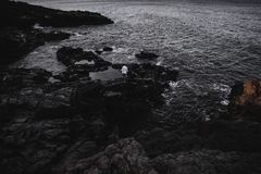 Anonymous traveler on dark rocks stock image