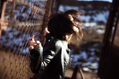 Anonymous woman portrait over fence Stock Image