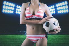 Anonymous woman with soccer ball at soccer field. Anonymous woman wearing bikini holding a soccer ball at soccer field in a stadium Royalty Free Stock Image