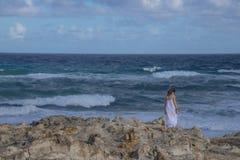 Anonymous woman standing near stormy sea stock photos