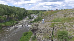 Anonymous woman standing on rocks above river stock video