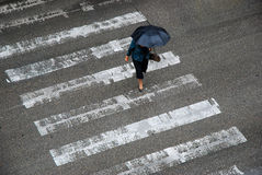 Anonymous woman with umbrella crossing street Royalty Free Stock Photography