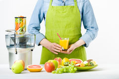 Anonymous woman wearing an apron, holding glass of freshly pressed juice, healthy lifestyle concept stock photos