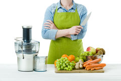 Anonymous woman wearing an apron, preparing fresh fruit juice using modern electric juicer, healthy lifestyle concept stock image
