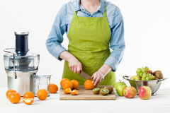 Anonymous woman wearing an apron, preparing fresh fruit juice using modern electric juicer, healthy lifestyle concept royalty free stock photography