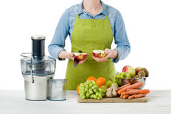 Anonymous woman wearing an apron, preparing fresh fruit juice using modern electric juicer, healthy lifestyle concept stock photography