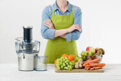 Anonymous woman wearing an apron, ready to start preparing healthy fruit juice using modern electric juicer. Healthy lifestyle concept on white background Royalty Free Stock Photography