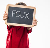 Anonymous young child holding school slate as shield against poux Royalty Free Stock Photo