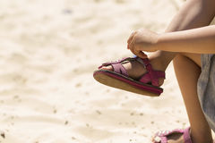 Anonymous young child puts her sandal back on Stock Images