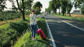 Anonymous Young lady hitchhiking on countryside road. stock video