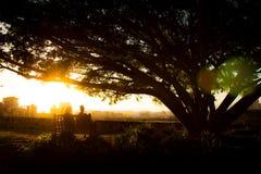 Anonymt folk som sitter på invallning under solnedgång arkivbilder