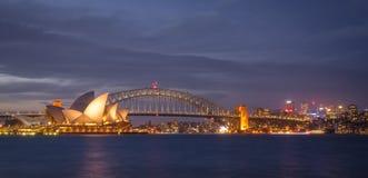 Anoramic widok Sydney pejzaż miejski przy półmrokiem przez schronienie od ogródu botanicznego widoku obrazy stock