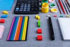 Anordnung für Bleistifte, Taschenrechner, Farben mit Bürsten, Zeichenstifte und ein Notizbuch Lizenzfreie Stockbilder