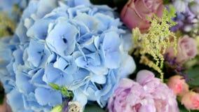 Anordnung für die verschiedenen Blumen von verschiedenen Farben, stehend auf Tabellen für eine Feiertagsdekoration stock video footage