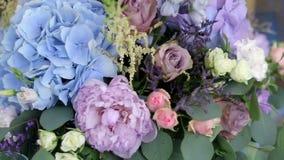 Anordnung für die verschiedenen Blumen von verschiedenen Farben, stehend auf Tabellen für eine Feiertagsdekoration stock video