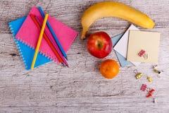 Anordnung für farbige Bleistifte und Notizbücher, Frucht, auf einem hölzernen Hintergrund Nahaufnahme Stockbilder