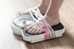 Anorexia and eating disorder concept. Feet tied up with measuring tape to a weight scale. Addiction and obsession to weight loss Stock Photography