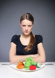 Anorexia, an eating disorder. Young girl sitting over a plate of vegetables and put into the mouth barbed wire royalty free stock photography