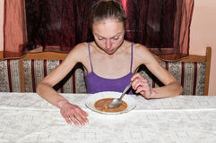 anorexia Het magere aan anorexie lijdende meisje die een lepel houden en bekijkt de plaat met voedsel stock foto