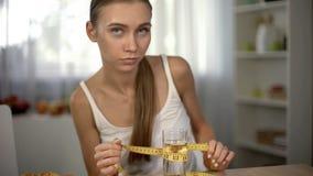 Anorexic dziewczyny pomiarowy szkło woda z taśmą, skołowany ciało, obsesja fotografia royalty free