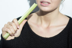 Anorexic girl eating a leek Royalty Free Stock Photography