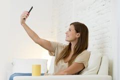 30 anos atrativos da mulher adulta que joga no sofá home do sofá que toma o retrato do selfie com telefone celular Imagens de Stock Royalty Free