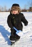 2 anos bonitos da criança que corre com a pá no inverno Imagem de Stock