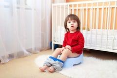 2 anos bonitos da criança que senta-se no urinol Foto de Stock