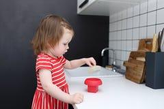 2 anos bonitos da menina da criança com o molde da omeleta do silicone no kitche Foto de Stock
