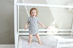 2 anos bonitos da menina em sua cama Foto de Stock