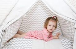 2 anos bonitos da menina que encontra-se na barraca da tenda em casa Fotografia de Stock
