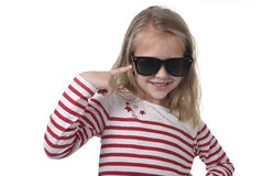6 a 8 anos bonitos de criança fêmea idosa com o cabelo louro que veste o sorriso grande dos óculos de sol feliz e brincalhão Fotografia de Stock Royalty Free