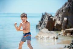 7 anos bonitos do menino idoso que tem o divertimento na praia tropical Foto de Stock