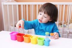 2 anos bonitos dos jogos do menino com cores Imagens de Stock Royalty Free