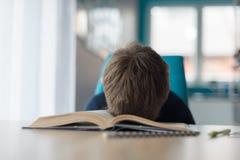 8 anos cansados do menino idoso que faz seus trabalhos de casa na tabela Imagens de Stock Royalty Free