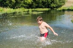 10 anos completos da nadada do menino no rio Imagem de Stock