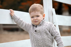 2 anos de bebê idoso em uma cerca de piquete branca b Fotos de Stock Royalty Free