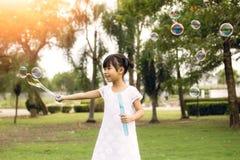 7 anos de cabelo preto velho no jogo branco do vestido e balão de sopro da bolha no parque Imagens de Stock