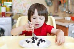 2 anos de criança comem o quark com a baga na cozinha Foto de Stock Royalty Free