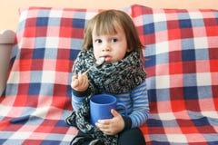 2 anos de criança doente no lenço e no copo de lã mornos do chá Fotografia de Stock Royalty Free