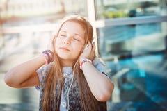 10 anos de criança feliz idosa da menina escutam a música Fotografia de Stock